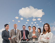 Seven business people, men and women, stand underneath a cloud with smaller clouds leading up from their heads to the cloud above mimicking a cartoon thought bubble in a stock photo about connection, the crowd, and commonalities over the Internet.