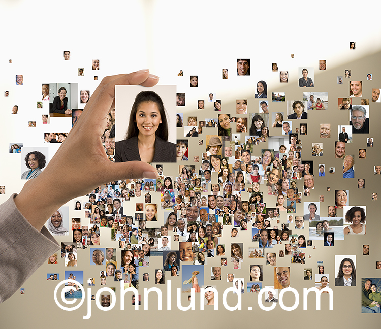Online selection from the crowd is one of the concepts illustrated by this photo of numerous portraits with a hand selecting one of the people images.