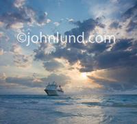 Picture of a cruise ship in calm tropical waters during a beautiful and dramatic sunset in a idealic setting for a once-in-a-lifetime vacation.