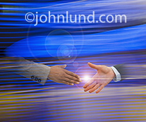 Two hands emerge from the ether about to connect in a handshake in an image about connection, teamwork, and communications technology.