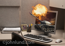 Cyber Warfare and video game play in the workplace are illustrated in this photo of a war tank and an explosion coming out of a computer display in an office cubicle.