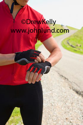 Picture of a mans torso as he adjusts his cycling gloves. The photo goes from his chin to just above his knees. The image of the cyclist is on the left side of the photo. The man is standing next to a country road trailing off into the distance.