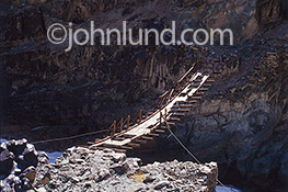 A dangerous footbridge, boards missing, stretches precariously across a chasm in the Himalyan Mountains.