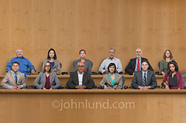 Twelve jury members sit in the jury box with deadpan, impassive expressions as they weigh the testimony and evidence presented to them in a stock photo about decisions, effective communications, judgements and our legal system.