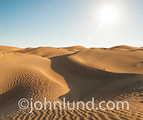 Desert sand dunes stretch out to the horizon in Death Valley in this stock photo about desolation, challenge, and drought.