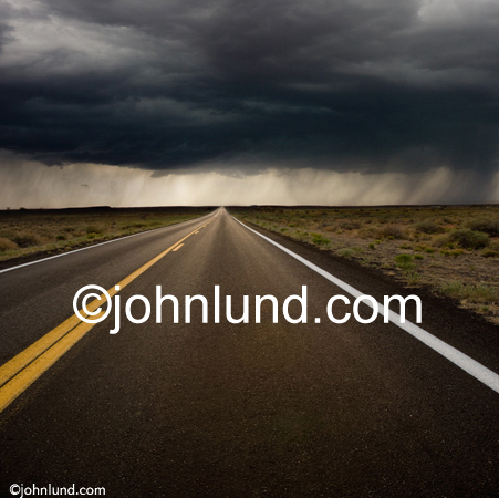Stock image of a road stretching into the distance beneath the clouds of a rain storm showing possibilities and the future.A long straight road with a double yellow line right down the middle. Long road picture.