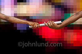 One hand passes a relay race baton to another against a background of pixelated lights in a stock photo about fast digital connections, networks and internet communications.