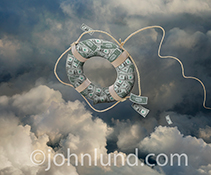 Business loans, cash flow solutions, and capital infusion are all dramatically shown in this stock photo of a life ring, created from money (dollar bills), sailing through a cloud bank (in a further nod to cloud computing).