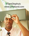 A black man in an office is putting a sticky note with a dollar sign on it on his forehead, or he is removing it. It isn't easy to tell.  The businessman is wearing a pink dress shirt  and a black and white necktie.
