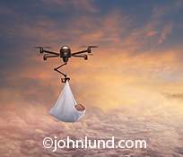 Drone pictures of a drone as it carries a new born baby through the sky in a concept stock photo about the ever increasing role drones play in this digital age.
