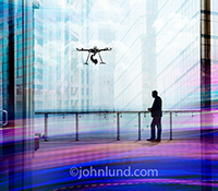 A businessman looks out over a metropolis while a drone hovers above him in an apparent corporate surveillance and espionage activity in a stock photo about drones and privacy issues.