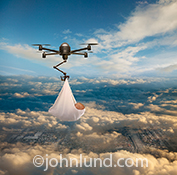 In this drone picture the drone is delivering a baby a la the iconic image of a stork deliverying a new borne. The drone is carrying the baby high above the clouds. Below one can see glimpses of a city through gaps in the cloud cover.