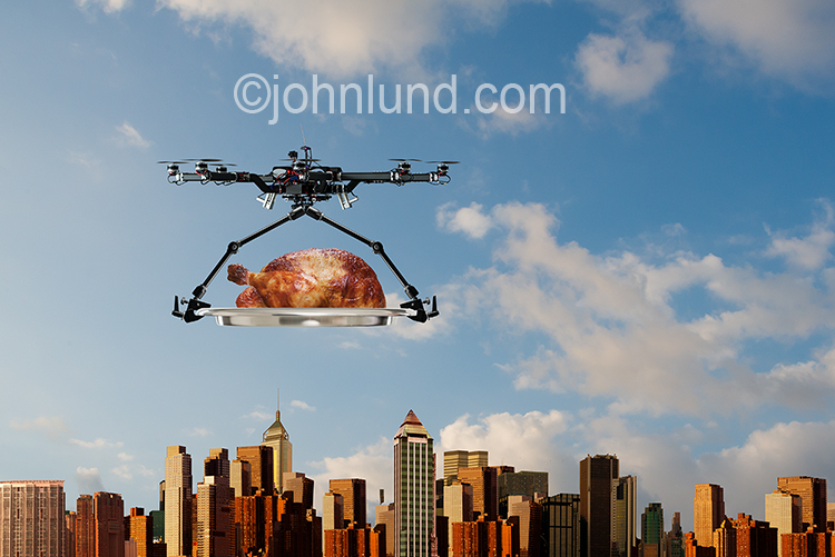 Drone food delivery is the concept behind this stock image of a drone delivering a thanksgiving turkey over a large metropolis.
