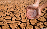 Picture of hands holding water over dry cracked earth. Dried mud rife with big cracks left when the water all dried up.