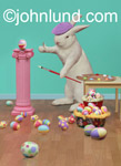 Funny animal picture and stock photo of an Easter Bunny painting easter eggs. He has a pink pedestal, and a purple cap.