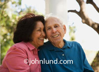 Pictures of older people. This photo is of a senior or elderly couple.  Happy smiling old man and old woman hugging outside on the porch.  The elderly couple is still in love and happy as clams.