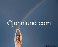 Stock photo of a young man holding up his hands in the air to symbolically catch a rainbow showing success and possibilities.