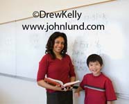 Stock photo of a teacher with her student.  A black female young adult elementary school teacher and her young male asian student smiling at the camera and standing in front of the whiteboard.  School room pictures for ads and advertising.