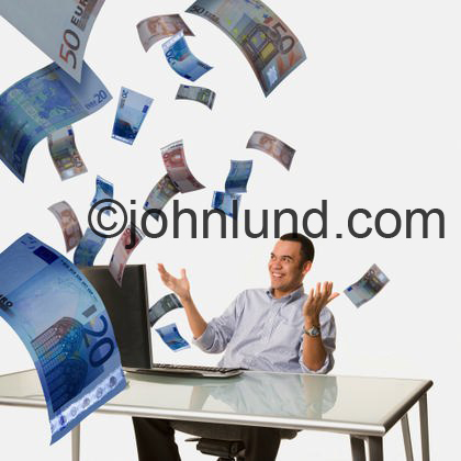 Stock photo of money, euros, flying out of a mans laptop computer.  He is smiling about all this easy money.  Various kinds of money bills are flying all over the place.