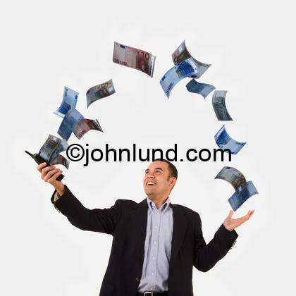 An ethnic business man has a cell phone in his hand and money is flowing out of the phone and forming an arch where the money is landing in his other hand. Money pics.