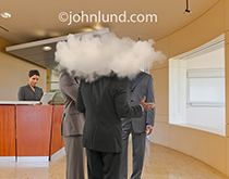 Three business executives stand in an upscale corporate reception area with their heads in a cloud in an image about cloud computing and possibly a lack of understanding.
