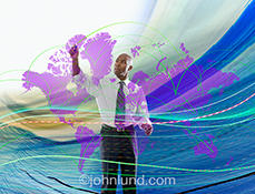 An executive maps out global business on a futuristic map of the continents as he is surrounded by streaming data and the flow of information in a stock photo about global business.