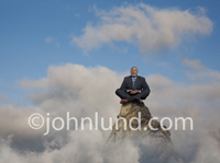 An African American businessman sits atop a mountain peak and meditates for insight into success.