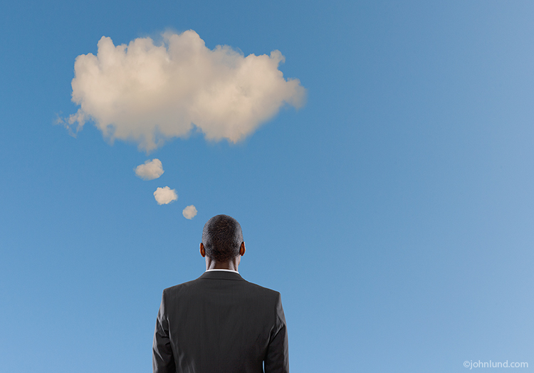 An African American executive looks out at the sky at a single overhead cloud with progressively smaller cloud puffs leading down to his head leaving the impression of a cloud-based thought bubble.