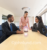 Three multi-ethnic business people in a conference room look intently at a crystal ball as they try to forecast the way forward.
