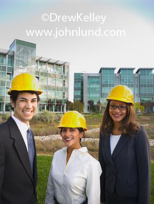 Pictures of mulit-ethnic top executives visiting a large construction job site. Three people in hard hats smiling at camera and wearing yellow hard hats.  Men and women in construction fotos.