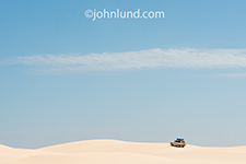 In an adventure travel image a four wheel drive truck climbs a sand dune on the Yemeni island of Socotra.
