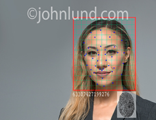 Facial recognition and security in action is the concept behind this stock photo of an Asian businesswoman with a grid and recognition points superimposed over her face along with an identification number and a fingerprint.