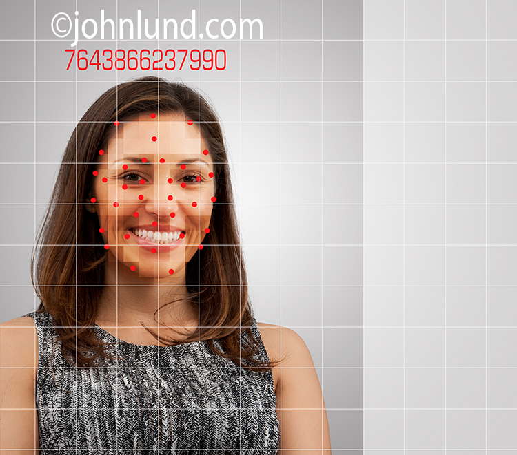 Facial recognition is the idea behind this stock photo showing a woman's face beneath a grid and recognition points and with an identification number over her head.
