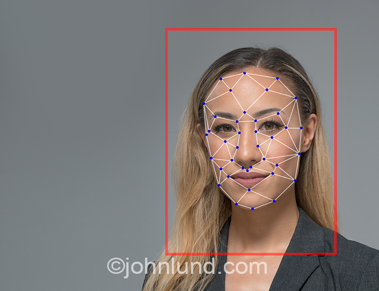Facial recognition technology is shown in this stock photo featuring an Asian American businesswoman with facial recognition points and polygons superimposed over her face.