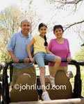 Image of a young girl and her grandparents standing up in the back of a jeep. The grandparents and grandaughter posing for a picture in an off-road trip while they are traveling on vacation. Smiling happy family members 4 wheeling on vacation.