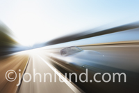 A sleek and futuristic convertible sports car flashes by in a blur of speed and power in this automotive concept photo.