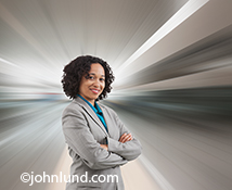 A woman executive stands confidently in a portrait while behind her the background zooms towards the viewer in a stock photo about the concepts of strong, successful women and the speed of business.