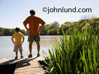 Stock photo of a father and is young son standing on a dock.  They both have their hands on their hips and have their backs to the camera. The father and son are looking out over the water.  Father is wearing orange shirt and shorts.