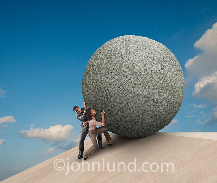 Financial planning for couples, along with personal finances, savings, banking and investment, are all illustrated in this stock photo of a man and woman struggling to push a giant ball of money up and over the lip of a precipice. They are just at the poi