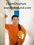 A happy smiling carpenter leaning against the sheet rock in an unfinished construction project.  He has his tool belt draped over his shoulder and is wearing an orange t shirt.  He has short wavy black hair. Average looking man.