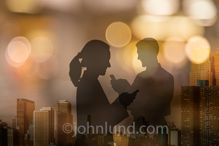 Flirting and dating on social media are just two of the concepts illustrated in this stock photo of a man and a woman, in silhouette, using that smart phones agains a backdrop of a city at night.