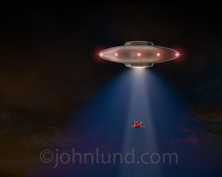 A beautiful woman is being pulled into a flying saucer with a tractor beam in this stock photo about UFO visits, mystery, and alien beings.