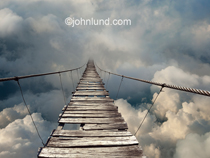A dangerous and rickety footbridge stretches away disappearing into a cloud bank in a metaphor for cloud computing, adventure, journey's, risk, and danger.