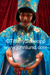 Forturne teller in blue mystic looking robes holding onto and gazing into her crystal ball. Picture of a psychic.