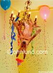 Funny animal stock photo of a Bloodhound swinging on a chandalier. Party animal with balloons, confetti and party hat. Stupid pet pictures.