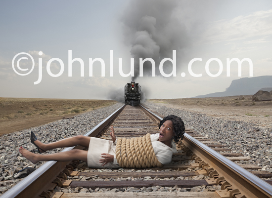 Woman is tied up and is lying across the railroad tracks as a train speeds towards her.