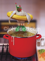 A chicken, wearing a mask, snorkel and swim fins prepares to jump into a pot of Chicken Soup in a funny fowl photo!