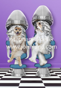 Two dogs, a Pomeranian and another undetermined long-haired breed, sit with foil in their fur under hair dryers in a beauty Salon in this Funny dog photo.