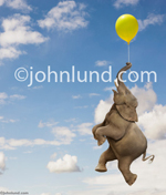 An elephant floats through the sky hanging on to a yellow balloon with his trunk in this funny elephant stock photo about the unexpected, contrasts and whimsical possibilities.