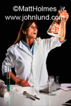 Photo of a woman scientist of Maltese descent is holding a flask up with what appears to be cold fusion or some sort of energy reaction going on in the flask or beaker. Science and science fiction photos.